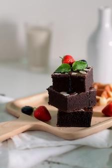 Przycięte ujęcie stosu czekoladowe ciasteczka z truskawkami i jagodami ozdobione na drewnianej tacy