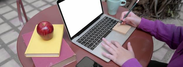 Przycięte ujęcie studentki odrabiania lekcji z pustego ekranu laptopa i książek