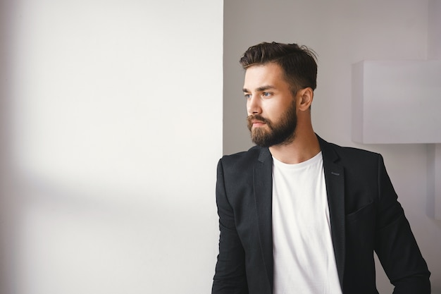 Przycięte ujęcie udanego, pewnego siebie, przystojnego młodego nieogolonego mężczyzny w stylowych, formalnych ubraniach pozujących przy oknie, stojącego na tle białej pustej ściany z miejscem na tekst