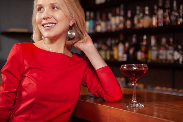 Przycięte ujęcie uroczej pięknej kobiety uśmiechającej się, odwracającej wzrok, odpoczywającej przy barze. atrakcyjna kobieta relaksuje przy barem po pracy