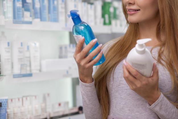 Przycięte ujęcie uśmiechniętej kobiety, czytanie etykiety na butelce z lekiem, zakupy w aptece