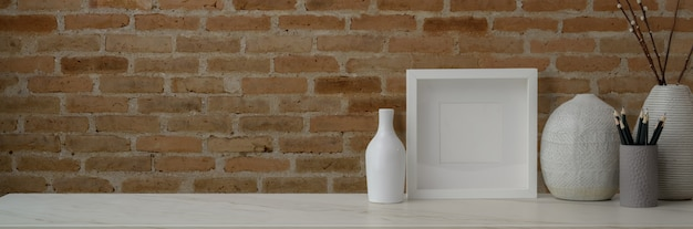 Przycięte ujęcie współczesnego obszaru roboczego z ramą, wazami ceramicznymi, materiałami biurowymi i przestrzenią do kopiowania