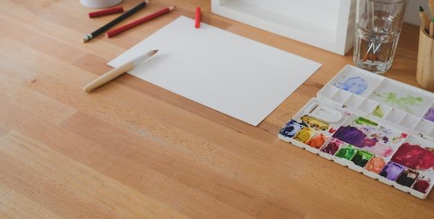 Przycięte ujęcie wygodnego miejsca pracy artysty z papieru do szkicu i narzędzi do malowania na drewnianym stole
