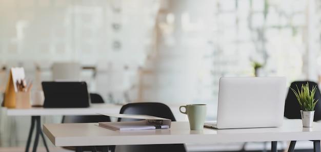 Przycięte ujęcie wygodnego miejsca pracy z laptopem i artykułami biurowymi