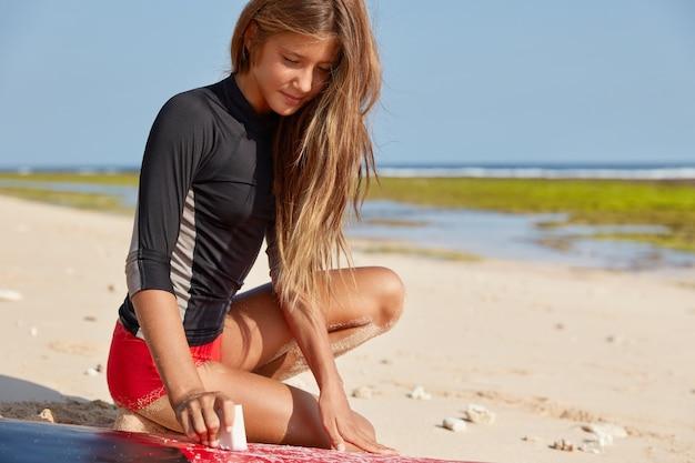 Przycięte ujęcie zachwyconej szczupłej kobiety woskowej deski surfingowej dla bezpiecznego surfowania i ochrony przed upadkiem