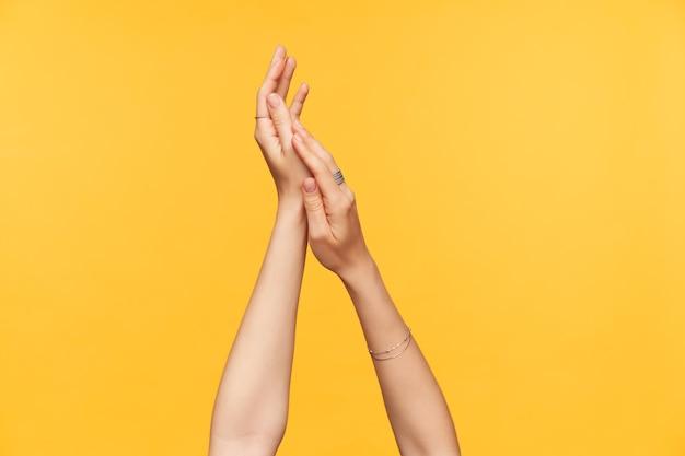Przycięte ujęcie zadbanych, jasnoskórych dłoni młodej kobiety podnoszonej podczas nakładania kremu, odizolowane na żółtym tle. koncepcja pielęgnacji rąk i ciała
