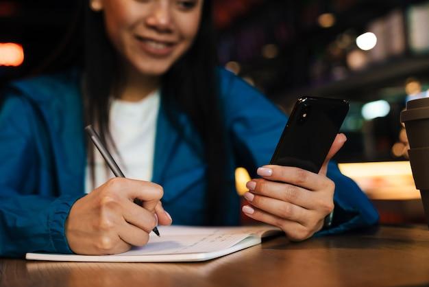 Przycięte zadowolona azjatycka kobieta robi notatki w terminarzu i używa telefonu komórkowego podczas siedzenia w kawiarni