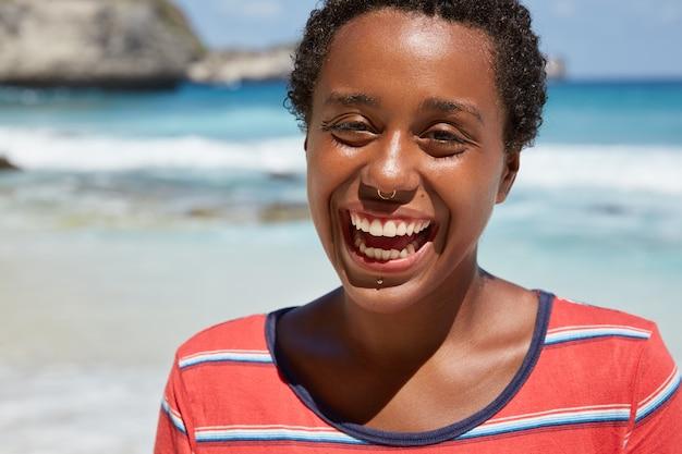 Przycięte zbliżenie czarnego nastolatka ma szczery szeroki uśmiech