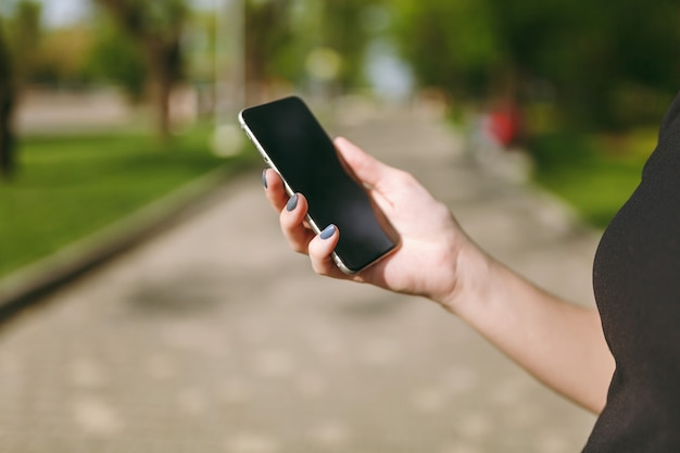 Przycięte zbliżenie dłoni kobiety trzymającej i używającej telefonu komórkowego, smartfona z pustym pustym ekranem w parku miejskim na zewnątrz