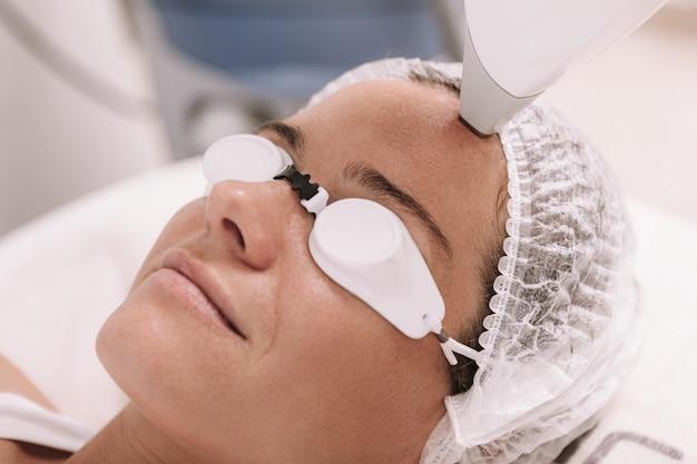 Przycięte zbliżenie dojrzałej kobiety, uśmiechając się, usuwając włosy twarzy laserem w klinice urody