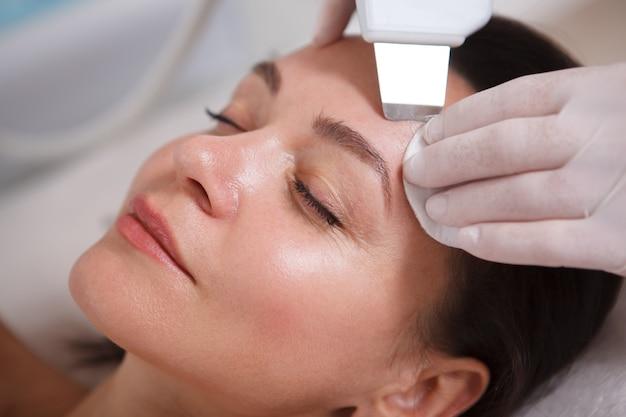 Przycięte zbliżenie dojrzałej pięknej kobiety, która otrzymuje ultradźwiękowy zabieg na twarz przez kosmetyczkę