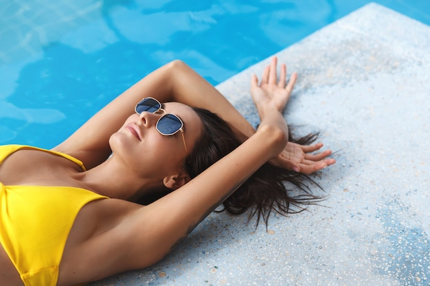 Przycięte zbliżenie kobiety w bikini, leżącej krawędzi basenu, opalającej się przy hotelowym basenie.