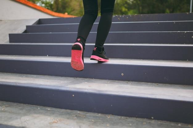 Przycięte zbliżenie nóg kobiety w odzieży sportowej, czarne i różowe trampki wykonujące ćwiczenia sportowe, wspinające się po schodach na zewnątrz