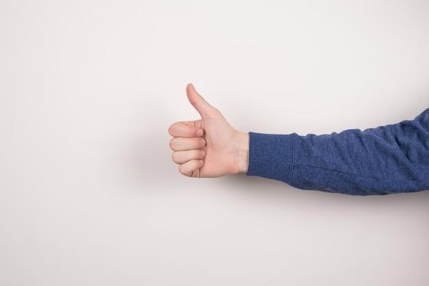 Przycięte zbliżenie obrazu przekonanego, przystojnego inteligentnego, inteligentnego biznesmena freelancera, który daje kciuk na białym tle szarej ścianie