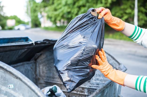 Przycięte zbliżenie osoby wkładającej worek na śmieci do kosza na śmieci na ulicy miasta