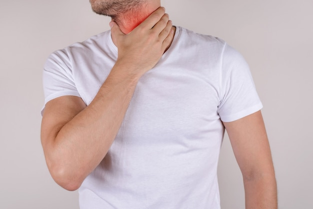Przycięte zbliżenie portret studio fotograficzne brodaty z zarost niezadowolony smutny zdenerwowany męski męski przystojny facet trzymający dotykający bolesną szyję nosić biały t-shirt na białym tle szary tło kopia przestrzeń
