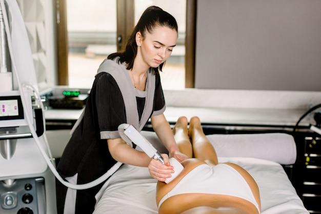 Przycięte zbliżenie profesjonalnej kosmetyczki za pomocą kawitacji ultradźwiękowej lub maszyny wałkowej na klientce.