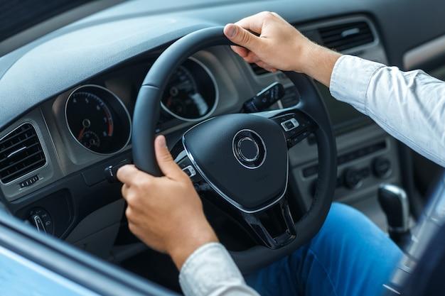 Przycięte zbliżenie strzał rąk mężczyzny na kierownicy