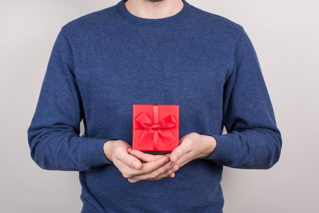 Przycięte zbliżenie wesoły dobry zadowolony pozytywny optymistyczny człowiek przedstawiający piękny ładny kwadratowy pojemnik na drogie prezenty w dłoniach odizolowane szare ściany