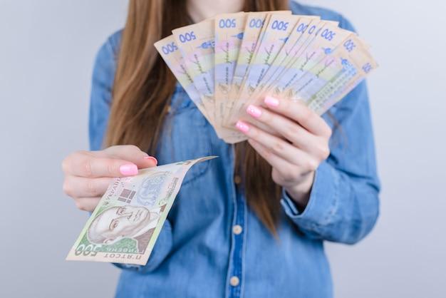 Przycięte zbliżenie zdjęcie bogatej zamożnej kobiety interesu trzymającej stos pieniędzy w rękach na białym tle szarym tle