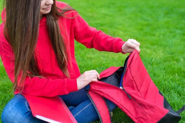 Przycięte zbliżenie zdjęcie pewnej siebie, inteligentnej, inteligentnej pięknej dziewczyny pakującej rzeczy do torby w torbie siedzącej na trawie