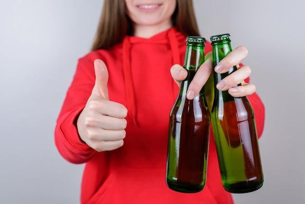 Przycięte zbliżenie zdjęcie pozytywnej, wesołej, dość pewnej siebie, zadowolenia z reklamy milenial używa kciuka trzymaj szkło w ręku na białym tle szarym tle