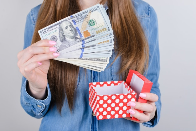 Przycięte zbliżenie zdjęcie szczęśliwej wesołej damy pokazującej szczupaka stos pieniędzy w ręku na białym tle szarym tle