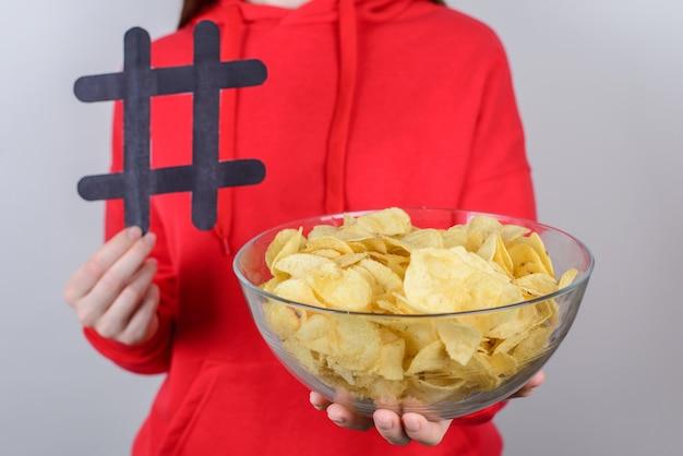 Przycięte zbliżenie zdjęcie wesołych podekscytowanych miłych atrakcyjnych ludzi posiadających duże duże smaczne pyszne chipsy trzymające w rękach pojedyncze szare tło