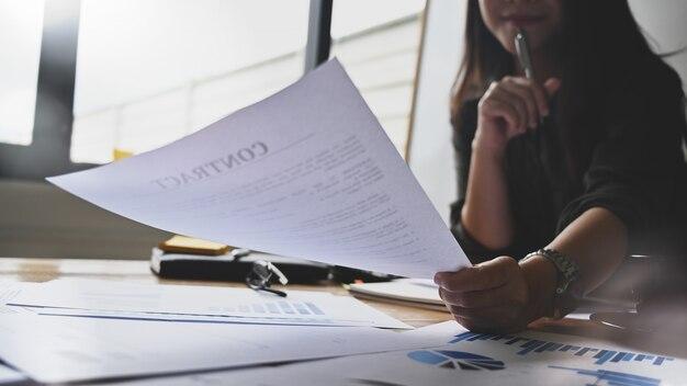 Przycięte zdjęcia młoda bizneswoman analiza finansów papierowa mapa.