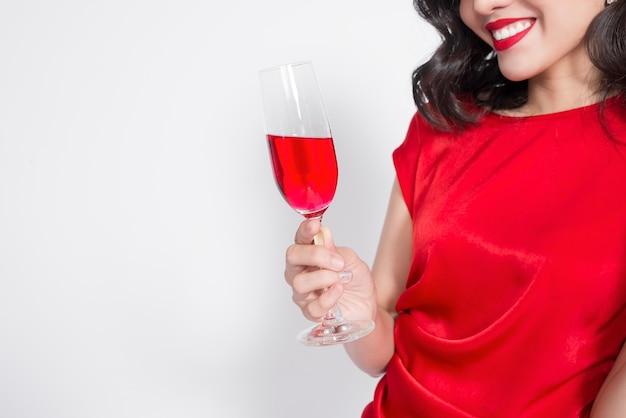 Przycięte zdjęcia młodych doceniają azjatyckie kobiety w czerwonej sukience trzymając kieliszek do wina.