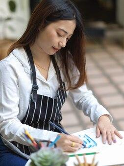 Przycięte zdjęcie artystki z malowaniem fartuch kolorowym ołówkiem na stoliku do kawy