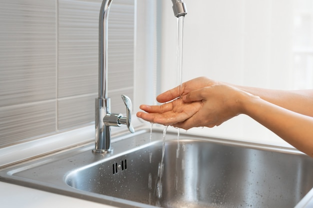 Przycięte zdjęcie azjatyckie kobiety mycie rąk w zlewie przed gotowaniem w kuchni w domu.