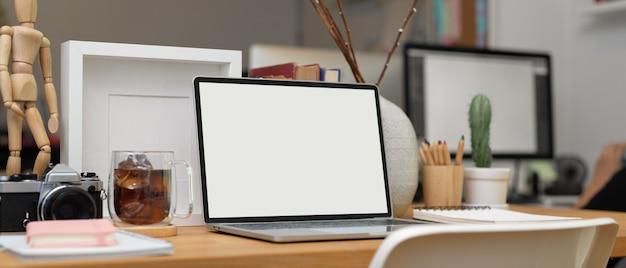 Przycięte zdjęcie biurka z laptopem, papeterii, materiałów biurowych i dekoracji w pokoju biurowym, ścieżka przycinająca.