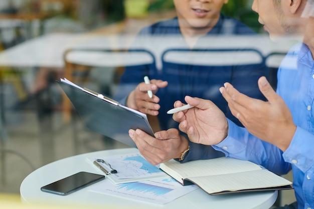 Przycięte zdjęcie biznesmenów omawiających raporty na spotkaniu i zapisujących plany w notatniku