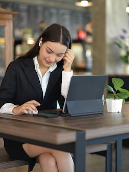 Przycięte zdjęcie bizneswoman z bezprzewodową słuchawką relaksującą ze smartfonem podczas pracy z tabletem
