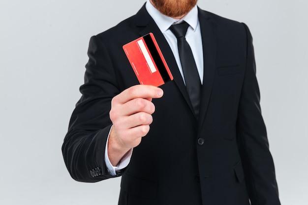 Przycięte zdjęcie człowieka biznesu w garniturze, trzymając w ręku kartę kredytową. na białym tle szarym tle