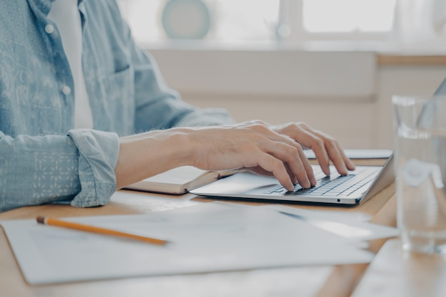 Przycięte zdjęcie człowieka przy użyciu komputera przenośnego w domu, męskie ręce pisania na klawiaturze na stole w kuchni. zbliżenie technologii w użyciu i pracy zdalnej online