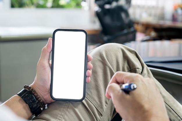 Przycięte zdjęcie człowieka ręki trzymającej pusty ekran smartphone biały siedzący przy biurku.
