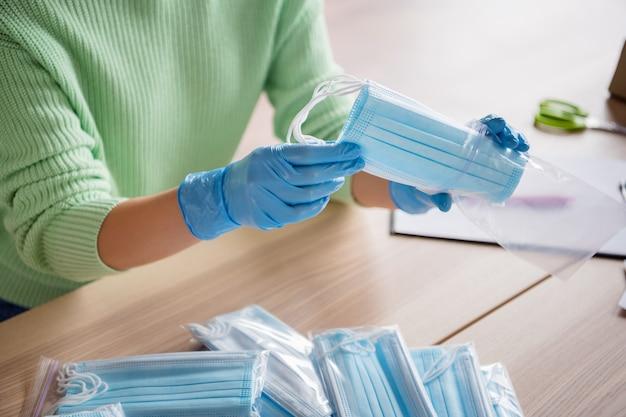 Przycięte zdjęcie damskich rąk rękawiczki lateksowe zorganizuj zamówienie masek przeciw grypie na twarz wysyłanie klienta przygotuj dostawę bezpieczeństwo antywirusowe umieść maski oddechowe w torbie na zamek błyskawiczny pozostań w biurze domowym w pomieszczeniu