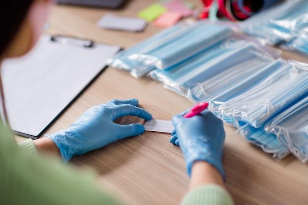 Przycięte zdjęcie damy ręce rękawiczki lateksowe trend organizacja biznesu pakowanie twarzy grypa maski medyczne własny produkt napisz zamówienie sprawdź adres przygotuj zestawy dostawa biuro domowe w pomieszczeniu