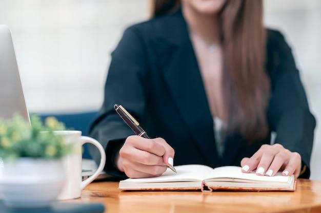 Przycięte zdjęcie dłoni kobiety za pomocą pióra pisania na notebooku, siedząc przy biurku.