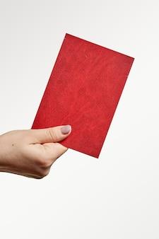 Przycięte zdjęcie dłoni trzymającej czerwony paszport pionowe zdjęcie osoby z dokumentem covid passp...