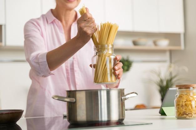 Przycięte zdjęcie dojrzałej kobiety gotowania.