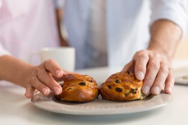 Przycięte zdjęcie dojrzałej miłości pary rodzinne jedzenie ciastek.