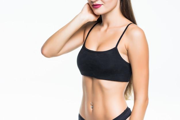 Przycięte zdjęcie dopasowanie kobiety tułowia kobiety w bikini na białym tle na białej ścianie. kobieta z doskonałymi mięśniami brzucha, pozowanie na białej ścianie