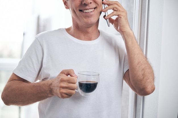 Przycięte zdjęcie dorosłego mężczyzny ze szczęśliwym uśmiechem trzymającego filiżankę kawy