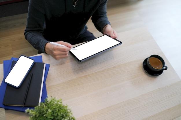 Przycięte zdjęcie dorywczo młody człowiek siedzi na drewnianej podłodze w salonie i za pomocą cyfrowego tabletu.