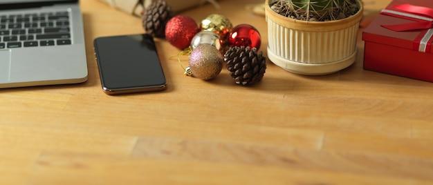 Przycięte zdjęcie drewniane biurko z laptopem smartphone i dekoracje w pokoju biurowym
