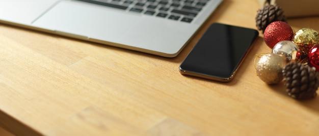 Przycięte zdjęcie drewniany stół z dekoracjami na smartfona laptopa i miejsce na kopię