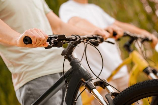 Przycięte zdjęcie dwóch dorosłych rowerzystów jeżdżących na rowerze w parku podczas porannego treningu